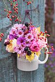 Kleiner Herbststrauß aus Astern, Rosen, Brombeeren, Hagebutten und Herbstlaub an Bretterwand gehängt