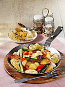 Fried potatoes with pancakes, Mediterranean vegetables and cheese