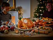 Familie beim traditionellen Weihnachtsessen mit Truthahn und Beilagen (England)