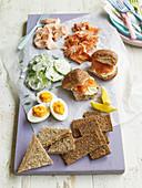 Picknick-Platte mit Lachssandwiches, Ei und Gurke