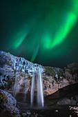 Aurora borealis over waterfall