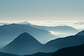 Aerial view of mountaintops over clouds