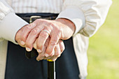 Close up of older man's hands on cane