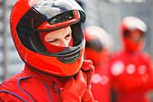 Racer tying on helmet on track