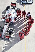 Racing team surrounding racer on track