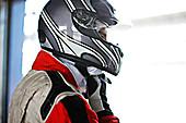 Racer tying on helmet in garage