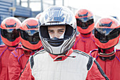 Racer with team standing outdoors