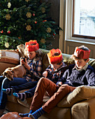 Children in paper crowns relaxing on sofa