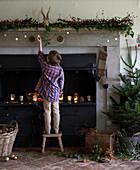 Boy decorating Christmas fireplace