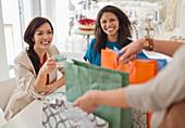 Woman showing friends shopping bags