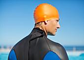 Triathlete wearing wetsuit and cap
