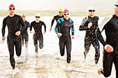 Swimmers in wetsuits walking in waves