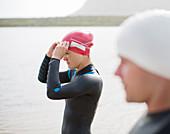 Triathletes pulling on goggles on beach