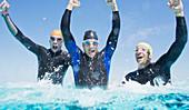 Triathletes in wetsuits splashing