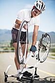 Man adjusting bicycle on rural road