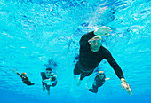 Triathletes in wetsuits underwater