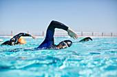 Triathletes in wetsuits racing in pool