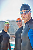 Triathletes wearing wetsuits outdoors