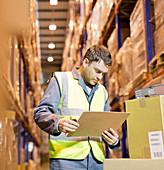 Worker reading clipboard in warehouse