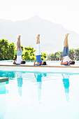 Men and woman practicing yoga poolside