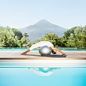 Woman stretching over fitness ball