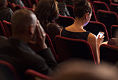 Woman using cell phone in theatre