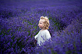 Boy walking in field of lavender