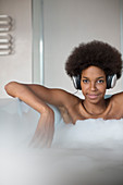 Woman listening to headphones in bath