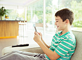 Boy using cell phone on sofa
