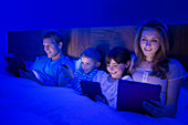 Family using technology in bed