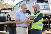 Roadside mechanic and man with paperwork
