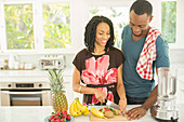 Couple slicing fruit next to blender