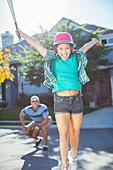 Cheering girl playing baseball in street