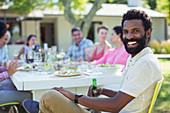 Man smiling at table outdoors