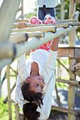 Girl climbing on monkey bars