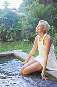 Woman dangling legs in pool