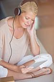 Woman using digital tablet and headphones