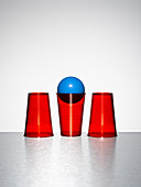 Blue ball in middle of three red cups