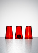 Ball under middle of three clear red cups