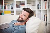 Smiling man listening to music on sofa
