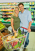 Couple smiling with full shopping cart