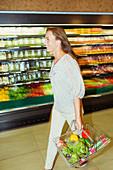Woman carrying full shopping basket