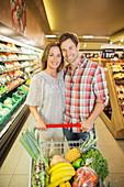 Couple pushing full shopping cart