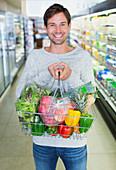 Man holding full shopping basket