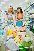 Women pushing full shopping cart together