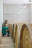 Vintners examining barrels