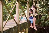 Siblings dangling feet off bridge