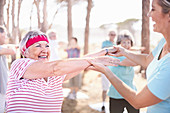 Yoga instructor guiding senior woman