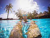Boy in sunny tropical swimming pool