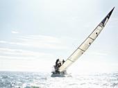 Sailboat tilting on sunny ocean